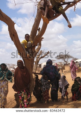 DADAAB,SOMALIA-AUGUST 15: Unidentified woman & children live in the Dadaab refugee camp where thousands of Somalis wait for help because of hunger on August 15, 2011 in Dadaab Somalia. - stock photo