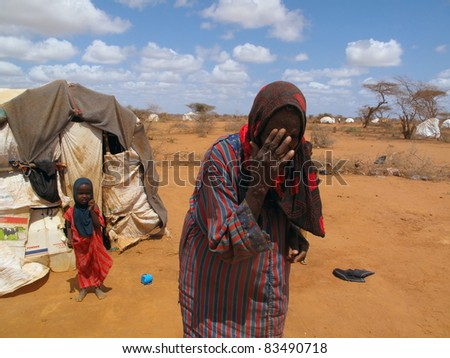 DADAAB,SOMALIA-AUGUST 15:Unidentified woman weeps as she walks away from tent in the Dadaab refugee camp where thousands of Somalis wait for help because of hunger on August 15,2011 in Dadaab,Somalia - stock photo
