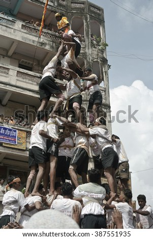 DADAR, MAHARASHTRA / INDIA - AUGUST 14, 2009 : A GROUP OF MEN, BUILDING A HUMAN TOWER DURING THE HINDU GOD KRISHNA FESTIVAL IN INDIA. - stock photo