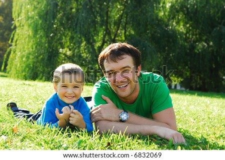 Daddy and son lying on the fresh green grass