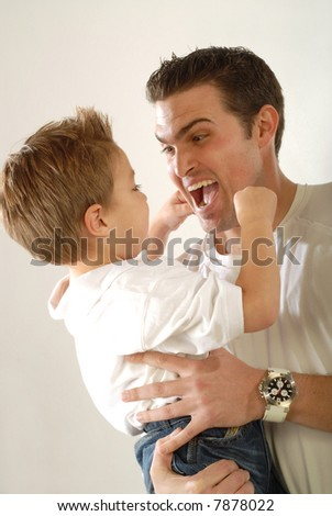 Daddy being silly and making faces with his young son - stock photo
