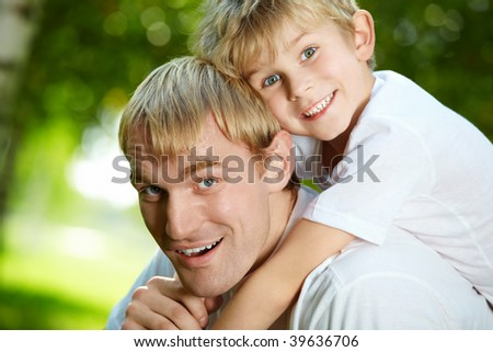 Daddy carries on a back of small son - stock photo