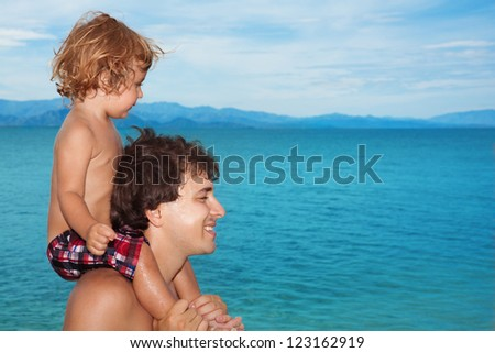 Daddy carry happy  kid on shoulders on seashore - stock photo