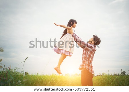 Daddy carrying his daughter with nature and sunlight, enjoyment family.