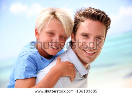Daddy giving piggyback ride to son by the beach - stock photo