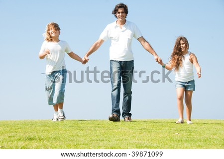 Daddy having fun with his children on meadow as he walks holding their hands - stock photo