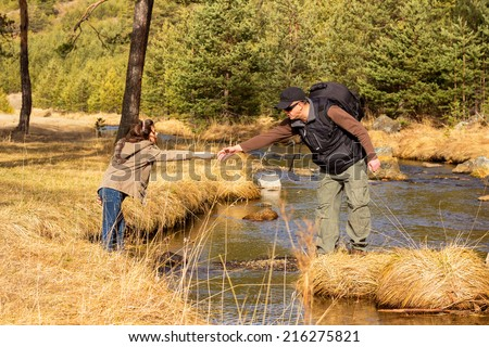Daddy helps daughter to cross the stream - stock photo