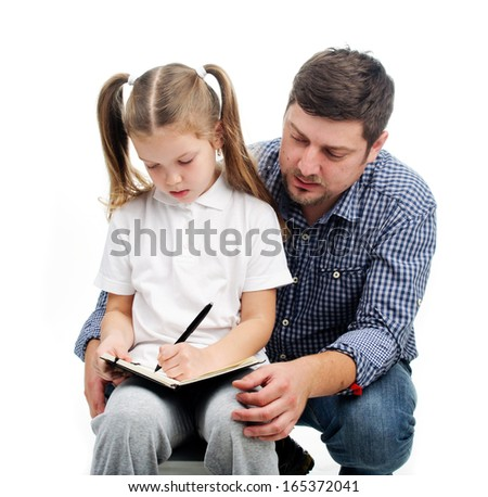 Daddy helps  his daughter with homework. - stock photo