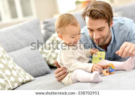 Daddy playing wih baby girl on sofa - stock photo