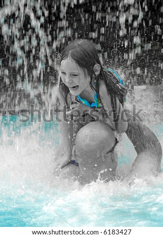 Daddy Playing with Daughter in Pool Waterfall - stock photo