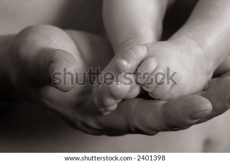 Daddy's hand holding baby's feet - stock photo
