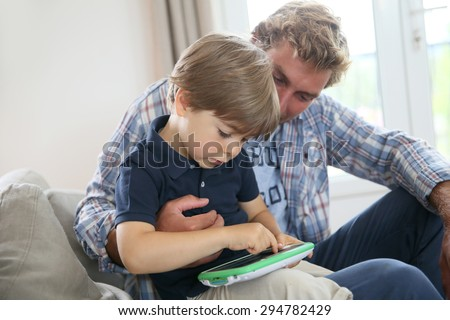 Daddy with kid playing with video game player - stock photo