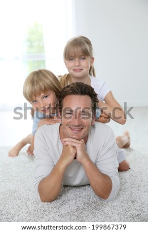 Daddy with kids laying on carpet - stock photo