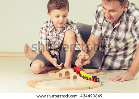 Daddy with little boy playing with toy train on the floor at the day time. Concept of friendly family. - stock photo