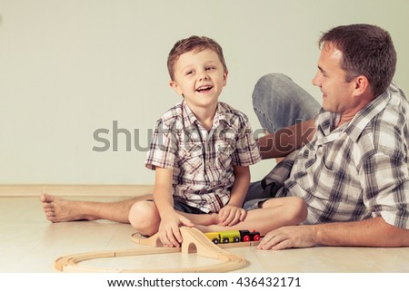 Daddy with little boy playing with toy train on the floor at the day time. Concept of friendly family.