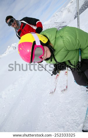 Daddy with young boy skiing down ski slope