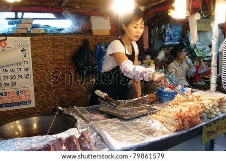 DAEPOHANG FISH MARKET - JUNE 06: A lady grills and cook seafood dishes for customers at her stall on June 06, 2011 in Daepohang, South Korea. This market is a tourist attraction at this port town.