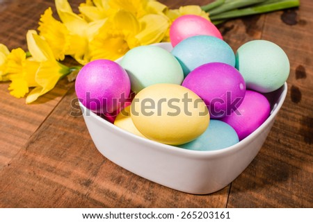 Daffodil flowers with bowl of dyed Easter eggs