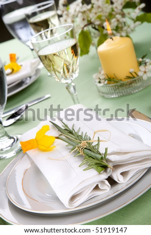 Daffodil table settings. Arrangements with yellow daffodil and fresh rosemary - stock photo