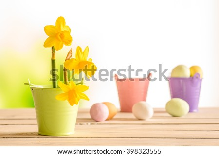 Daffodils in the easter on a wooden table with easter eggs in the background - stock photo