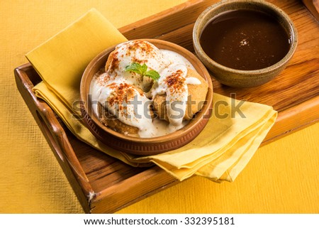 dahi vada or dahi bhalla, indian snacks, served with tamarind chutney, top view on white background - stock photo