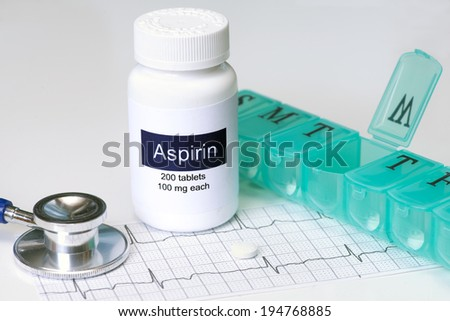 Daily aspirin dose with stethoscope and pill dispenser. - stock photo