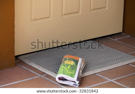 Daily magazine waiting to be picked up outside home entrance door - stock photo
