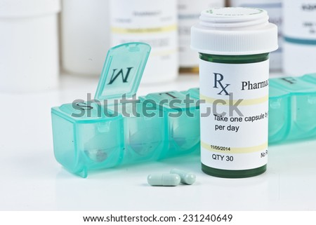 Daily medication dispenser with green prescription bottle and pills. - stock photo