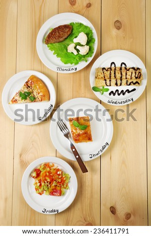 Daily menu. Plates with food on table - stock photo