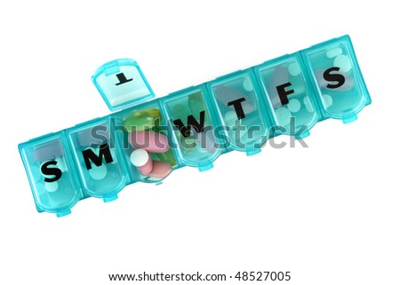Daily pill box with medications and nutritional supplements. - stock photo