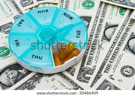 Daily pill holder sitting on one dollar bill background, Costs of medication