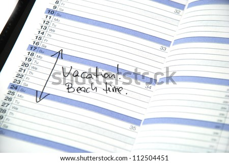 daily planner showing scheduled vacation time at the beach - stock photo