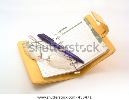 daily planner with glasses and pen