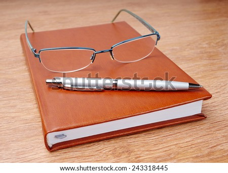 Daily planner with glasses and pen on the table - stock photo