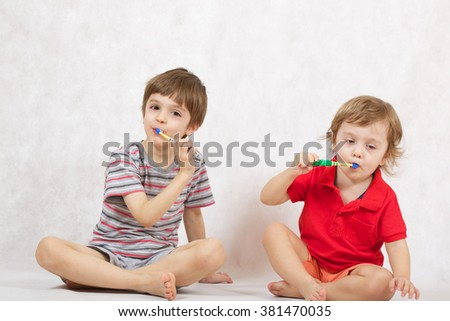 Daily teeth care in childhood. Boys are cleaning their teeth - stock photo