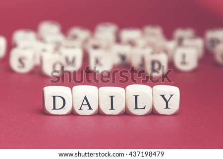 Daily word written on wood cube with red background - stock photo