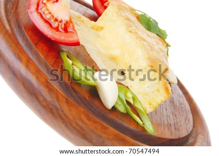 dairy food : cheese casserole triangle served on wood plate with tomatoes, capers, and chives isolated over white background