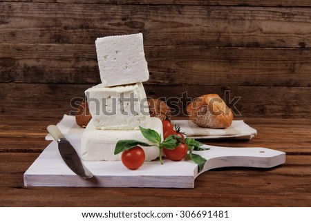 dairy healthy food fresh white greek goat sheep feta cheese on wood cutting plate with cherry tomatoes and french bun over dark wooden table - stock photo