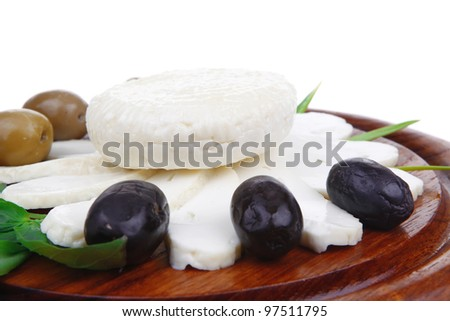 dairy products : feta white cheese sliced on cut board with olives and basil leaves isolated over white background