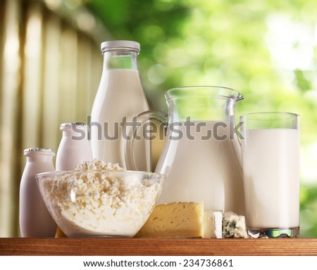 Dairy products on old wooden table. Behind - rural background blur. - stock photo