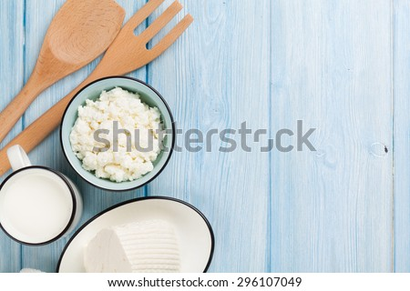 Dairy products on wooden table. Milk, cheese, curd cheese and butter. Top view with copy space - stock photo