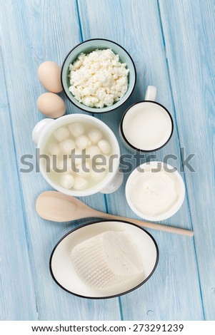 Dairy products on wooden table. Sour cream, milk, cheese, egg, yogurt and butter. Top view - stock photo
