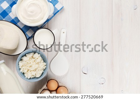 Dairy products on wooden table. Sour cream, milk, cheese, eggs and yogurt. Top view with copy space - stock photo