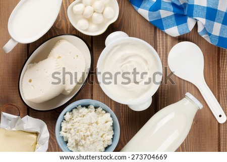 Dairy products on wooden table. Sour cream, milk, cheese, yogurt and butter. Top view - stock photo