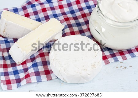 Dairy products. Sour cream, camembert and brie with checkered napkin on light blue wooden table.