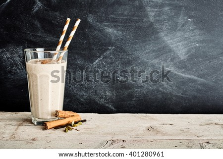 Dairy smoothie with two swirl colored straws and a sprinkle of cinnamon in a large glass on a long table - stock photo