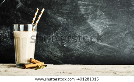 Dairy Vanilla drink in a large glass beside cinnamon sticks on a long rustic table by dusty chalkboard - stock photo