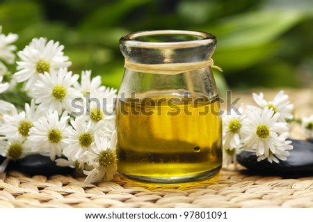 daisies flower and massage oil with stones on wicker mat - stock photo