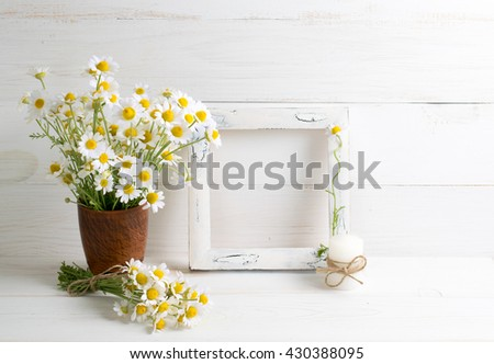 Daisy flowers bouquet with photo frame and candle on white wooden shabby board. Home interior.
