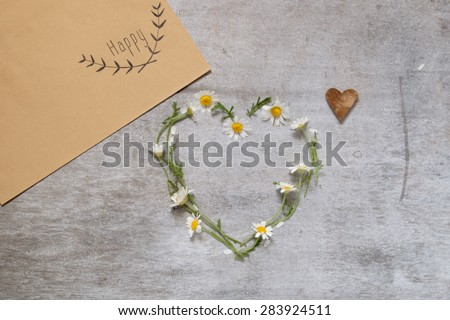 Daisy love symbol on old wooden background envelope with flowers and an inscription happy - stock photo